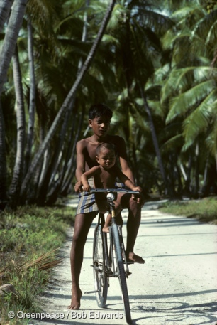 A youth and child on a bicycle at Abemama, Kiribati, South Pacific.