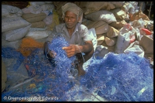 Old man sitting amongst a pile of blue plastic