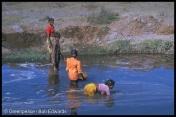 Villagers clearing silt from effluent stream of central pulp mill Surat distrtict, Gujarat