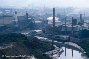 """Asua river near Bilbao Northern Spain, showing a copper smelter and the ASER factory on the left. ASER imports steel dust for recycling. Bilbao is a heavily industrialised city in the Basque region and is now a centre for disposing of imported hazardous wastes using the """"recycling"""" loophole in European Community regulations."""